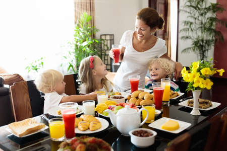 Photo pour Healthy family breakfast at home. Mother and kids eating tropical fruit, toast bread, cheese and sausage. Children drink fresh pressed juice on sunny morning. Mom, boy, girl and baby eat breakfast. - image libre de droit
