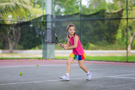 Foto de Child playing tennis on indoor court. Little girl with tennis racket and ball in sport club. Active exercise for kids. Summer activities for children. Training for young kid. Child learning to play. - Imagen libre de derechos