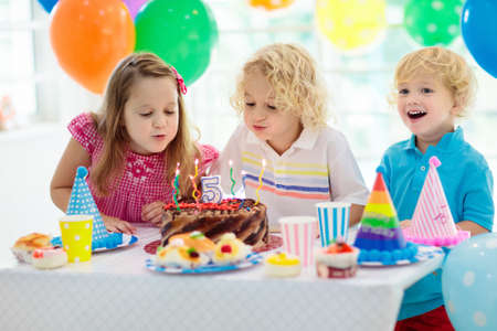 Foto de Kids birthday party. Child blowing out candles on colorful cake. Decorated home with rainbow flag banners, balloons. Farm animals theme celebration. Little boy celebrating birthday. Party food. - Imagen libre de derechos