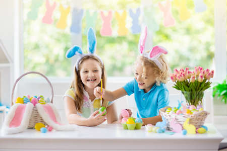 Photo for Kids dyeing Easter eggs. Children in bunny ears dye colorful egg for Easter hunt. Home decoration with flowers, basket and rabbit for spring holiday celebration. Little boy and girl decorate home. - Royalty Free Image