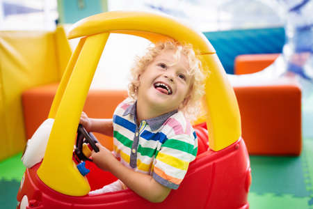 Photo for Child riding toy car. Little boy playing with big bus. Kid driving plastic truck in indoor playground or kindergarten. Toddler at day care play room. Toys for little boys. Daycare amusement center. - Royalty Free Image