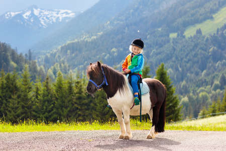 Photo for Kids riding pony in the Alps mountains. Family spring vacation on horse ranch in Austria, Tirol. Children ride horses. Kid taking care of animal. Child and pet. Little boy in saddle on pony. - Royalty Free Image