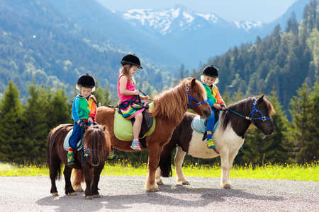 Photo for Kids riding pony in the Alps mountains. Family spring vacation on horse ranch in Austria, Tirol. Children ride horses. Kid taking care of animal. Child and pet. Little girl and boy in saddle on pony. - Royalty Free Image