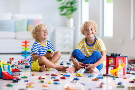 Photo pour Kids play with toy cars in white room. Little boy playing with car and truck toys. Vehicle and transportation game for children. Kid with parking garage. Child having fun at home or daycare. - image libre de droit