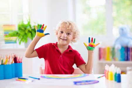 Foto de Kids paint. Child painting in white sunny study room. Little boy drawing rainbow. School kid doing art homework. Arts and crafts for kids. Paint on children hands. Creative little artist at work. - Imagen libre de derechos