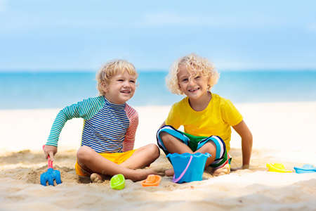 Photo pour Kids playing on tropical beach. Children play at sea on summer family vacation. Sand and water toys, sun protection for young child. Little boy digging sand, building castle at ocean shore. - image libre de droit