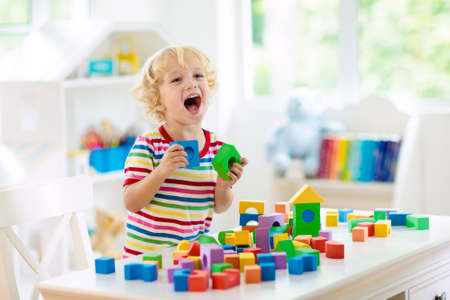 Photo pour Kid playing with colorful toy blocks. Little boy building tower of block toys. Educational and creative toys and games for young children. Baby in white bedroom with rainbow bricks. Child at home. - image libre de droit
