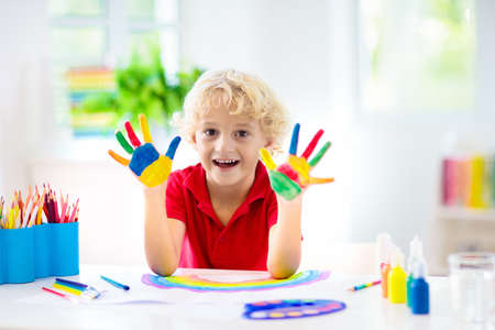 Photo for Kids paint. Child painting in white sunny study room. Little boy drawing rainbow. School kid doing art homework. Arts and crafts for kids. Paint on children hands. Creative little artist at work. - Royalty Free Image