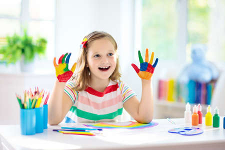 Photo pour Kids paint. Child painting in white sunny study room. Little girl drawing rainbow. School kid doing art homework. Arts and crafts for kids. Paint on children hands. Creative little artist at work. - image libre de droit