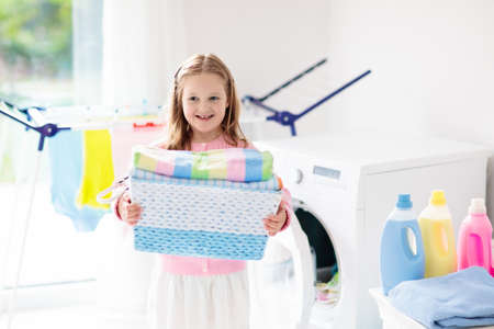 Photo pour Child in a laundry room with washing machine or tumble dryer. Kid helping with family chores. Modern household devices and washing detergent in white sunny home. Clean washed clothes on drying rack. - image libre de droit