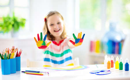 Foto de Kids paint. Child painting in white sunny study room. Little girl drawing rainbow. School kid doing art homework. Arts and crafts for kids. Paint on children hands. Creative little artist at work. - Imagen libre de derechos