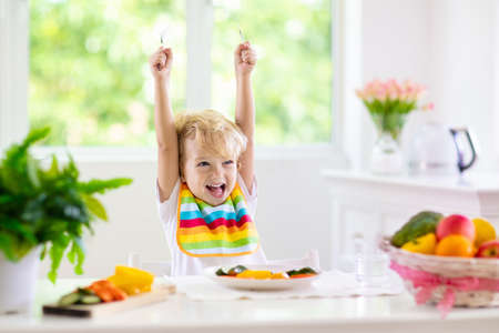 Photo pour Child eating vegetables sitting in white high chair. Solid food for baby. Little boy eating healthy vegetable lunch of steam cooked carrots. Nutrition for toddler and preschooler. Kids eat fruit. - image libre de droit