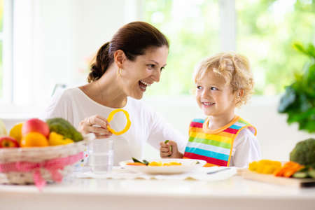 Photo pour Mother feeding child vegetables. Mom feeds kid in white kitchen with window. Baby boy sitting in high chair eating healthy lunch of steamed carrot and broccoli. Nutrition, vegetarian diet for toddler - image libre de droit