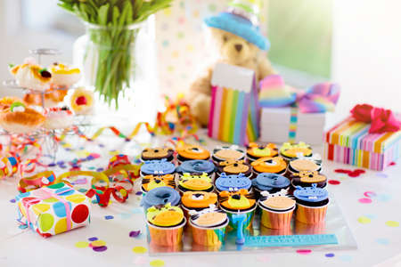 Photo pour Cupcakes for kids birthday celebration. Jungle animals theme children party. Decorated room for boy or girl kid birthday. Table setting with presents, gift boxes, confetti and sweets. Pastry for child - image libre de droit