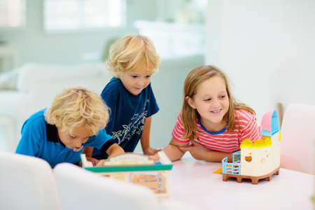 Photo for Kids play board game. Group of preschool children playing educational game sitting at white desk in sunny class room. Boy and girl with new toys. Child at home or daycare. Games for school kid. - Royalty Free Image