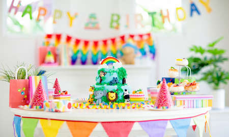 Foto de Cake for kids birthday celebration. Jungle animals theme children party. Decorated room for boy or girl kid birthday. Table setting with presents, gift boxes, confetti and sweets. Pastry for child - Imagen libre de derechos