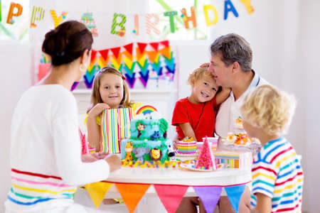 Photo for Kids birthday party. Child blowing candles on cake and opening presents on jungle theme celebration. Family celebrating at home. Mother, father, boy and girl open gifts, eat cakes. Sweets for children - Royalty Free Image