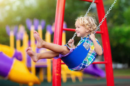 Photo pour Child playing on outdoor playground in rain. Kids play on school or kindergarten yard. Active kid on colorful swing. Healthy summer activity for children in rainy weather. Little boy swinging. - image libre de droit
