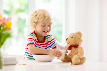 Photo pour Child having breakfast. Kid feeding teddy bear toy, drinking milk and eating cereal with fruit. Little boy at white dining table in kitchen at window. Kids eat. Healthy nutrition for young kids. - image libre de droit
