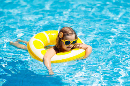 Photo pour Child in swimming pool on inflatable yellow lemon ring. Little girl learning to swim with orange float. Water toy for baby and toddler. Healthy outdoor sport activity for children. Kids beach fun. - image libre de droit