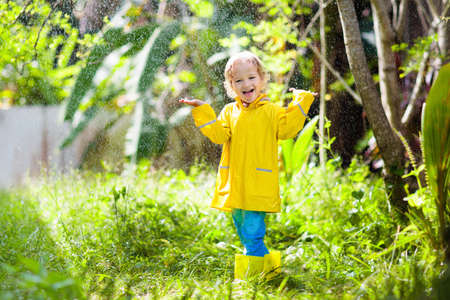 Photo for Child playing in the rain on sunny autumn day. Kid under heavy shower with yellow duck umbrella. Little boy with duckling waterproof shoes. Rubber wellies boots. Fall outdoor activity by rainy weather - Royalty Free Image
