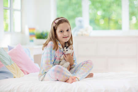 Foto de Child playing with baby cat on bed in white bedroom. Kid holding white kitten. Little girl in pajamas with cute pet animal at home. Kids play with cats. Children and domestic animals pets. - Imagen libre de derechos