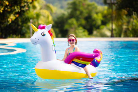 Photo pour Child on unicorn float in swimming pool of tropical resort. Kids swim and play with inflatable water toys. Little girl playing on pink pony ring on family summer vacation on exotic island. Beach fun. - image libre de droit