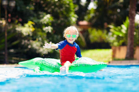 Photo pour Child playing in swimming pool. Kids learn to swim. Little baby boy with inflatable toy float playing in water on summer vacation in tropical resort. Kid with toy crocodile on beach holiday. - image libre de droit