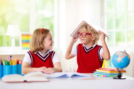 Photo pour Kids go back to school. Children study and learn for preschool. Boy and girl of elementary class doing homework. Bedroom with desk, books and globe for young child. Kid learning to read and write. - image libre de droit