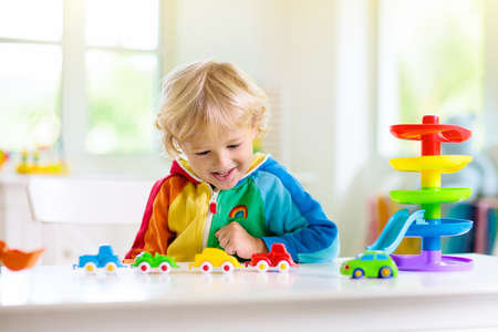 Photo pour Little boy playing toy cars. Young kid with colorful educational vehicle and transport toys. Child driving car to rainbow parking garage. Kids at home or daycare. Kindergarten or preschool game. - image libre de droit