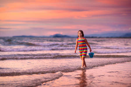 Photo pour Child playing on ocean beach. Kid jumping in the waves at sunset. Sea vacation for family with kids. Little girl running on tropical beach of exotic island during summer holiday. - image libre de droit