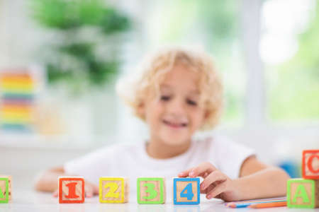 Foto de Child learning letters and numbers. Kid with colorful wooden abc blocks. Little boy spelling words with educational block toys. Kids doing school homework at white desk. Bedroom for preschool children - Imagen libre de derechos