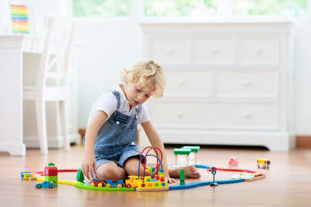 Photo pour Kids play with wooden railway. Child with toy train. Educational toys for young children. Little boy building railroad tracks on white floor at home or kindergarten. Cute kid playing cars and engine. - image libre de droit