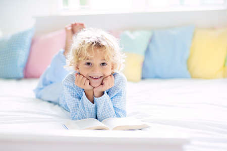 Photo pour Child reading book in bed in white sunny bedroom with window. Children read books. Kids room. Little blond curly boy in pajamas at home. Bedding and sleepwear for nursery. Kid with toy. - image libre de droit
