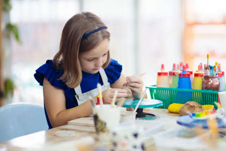 Photo pour Child working on pottery wheel. Kids arts and crafts class in workshop. Little girl creating cup and bowl of clay. Creative activity for young children in school. Cute kid forming toy with ceramic. - image libre de droit