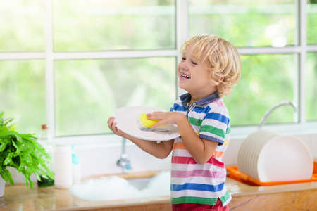 Photo pour Child washing dishes. Home chores. Kid in white kitchen cleaning plates after lunch at window. - image libre de droit