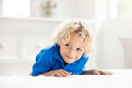 Photo pour Child playing hide and seek. Little boy on white bed. Kids at home. - image libre de droit