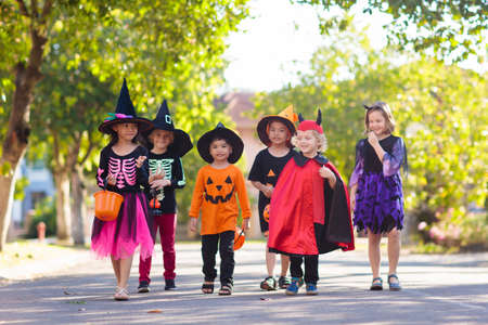 Photo pour Child in Halloween costume. Mixed race Asian and Caucasian kids trick or treat on suburban street. Little boy and girl with pumpkin lantern and candy bucket. Baby in witch hat. Autumn holiday fun. - image libre de droit