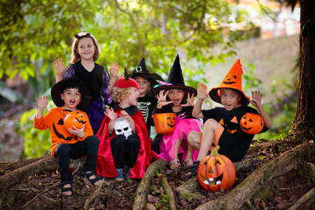 Foto per Child in Halloween costume. Mixed race Asian and Caucasian kids trick or treat on suburban street. Little boy and girl with pumpkin lantern and candy bucket. Baby in witch hat. Autumn holiday fun. - Immagine Royalty Free