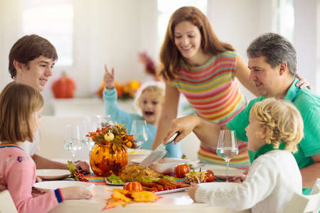 Photo for Family with kids eating Thanksgiving dinner. Roasted turkey and pumpkin pie on dining table with autumn decoration. Parents and children having festive meal. Father and mother cutting meat. - Royalty Free Image