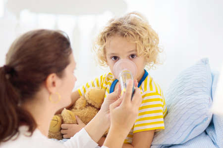 Photo pour Sick little boy with asthma medicine. Mother with ill child lying in bed. Unwell kid with chamber inhaler for cough treatment. Flu season. Parent in bedroom or hospital room for young patient. - image libre de droit