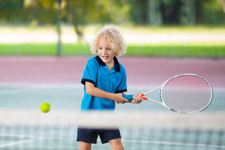 Foto de Child playing tennis on indoor court. Little boy with tennis racket and ball in sport club. Active exercise for kids. Summer activities for children. Training for young kid. Child learning to play. - Imagen libre de derechos