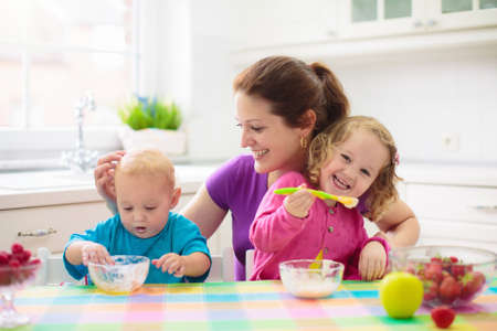 Photo for Mother feeding child fruit and yoghurt. Mom feeds kid in white kitchen. Baby boy and girl sitting in high chair eating healthy lunch of cereal and milk. Nutrition, healthy breakfast for toddler - Royalty Free Image