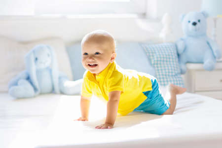 Photo pour Baby playing on parents bed. Cute funny little boy learning to crawl in white sunny nursery. Infant and toddler room interior. Bedding and toys for kids. Children play at home. Baby bedroom. - image libre de droit