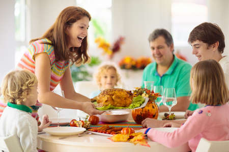 Photo pour Family with kids eating Thanksgiving dinner. Roasted turkey and pumpkin pie on dining table with autumn decoration. Parents and children having festive meal. Father and mother cutting meat.  - image libre de droit