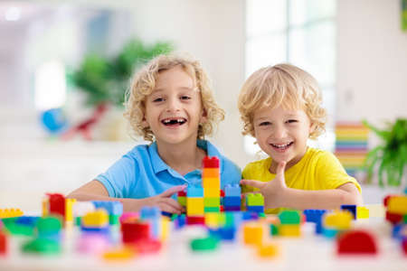 Foto de Kids play with colorful blocks. Little boy building tower at home or day care. Educational toy for young child. Construction creative game for baby or toddler kid. Mess in kindergarten playroom. - Imagen libre de derechos