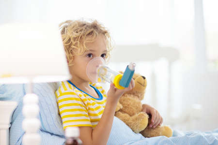 Photo pour Sick little boy with asthma medicine. Ill child lying in bed. Unwell kid with chamber inhaler for cough treatment. Flu season. Bedroom or hospital room for young patient. Healthcare and medication. - image libre de droit