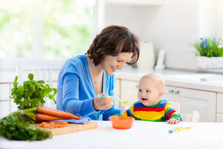Foto für Mother feeding child. First solid food for young kid. Fresh organic carrot for vegetable lunch. Baby weaning. Mom and little boy eat vegetables. Healthy nutrition for children. Parents feed kids. - Lizenzfreies Bild