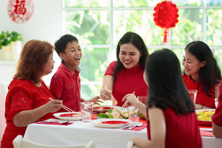 Foto de Chinese New Year celebration. Family celebrating winter holiday. Traditional festive dinner in China. Parents, grandparent and kids eating and giving red ang pao envelopes to children. Home decoration - Imagen libre de derechos