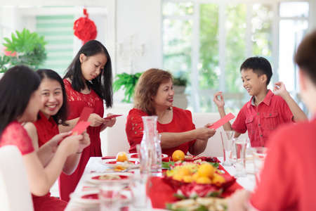Photo pour Chinese New Year celebration. Family celebrating winter holiday. Traditional festive dinner in China. Parents, grandparent and kids eating and giving red ang pao envelopes to children. Home decoration - image libre de droit